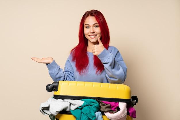 広告を挿入するために手のひらにcopyspaceの想像を保持しているベージュの壁と親指を上に分離された服の完全なスーツケースを持つ旅行者女性