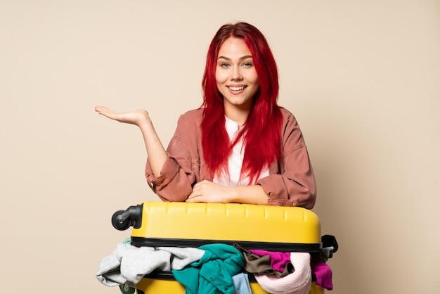 広告を挿入する手のひらに架空のcopyspaceを保持しているベージュに分離された服の完全なスーツケースを持つ旅行者の女の子