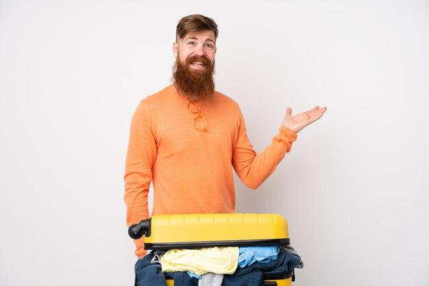 手のひらに架空のcopyspaceを保持している孤立した白い壁に服がいっぱいのスーツケースを持つ旅行者男