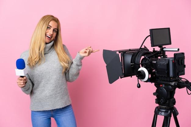 Репортер женщина, держащая микрофон и сообщения о новостях на изолированной розовой стене, держащей воображаемое copyspace на ладони, чтобы вставить объявление