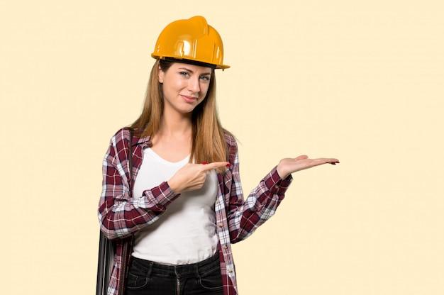 孤立した黄色の壁に広告を挿入する手のひらに想像上のcopyspaceを保持している建築家女性