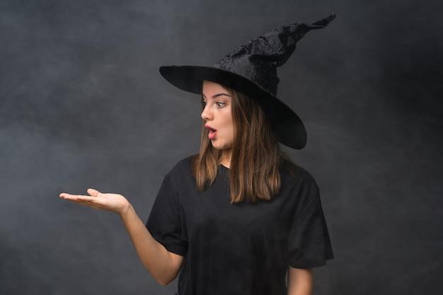 Девушка с костюмом ведьмы для вечеринок хэллоуина над изолированной темной стеной, держащей copyspace мнимой на ладони