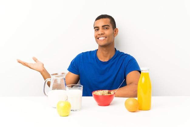 Молодой человек завтрака в таблице, держа воображаемое copyspace на ладони