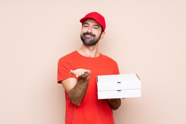 Молодой человек держит пиццу держа воображаемое copyspace на ладони, чтобы вставить объявление