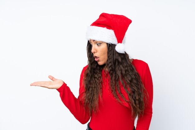 Девушка с шляпой рождества над изолированным белым держа copyspace мнимым на ладони