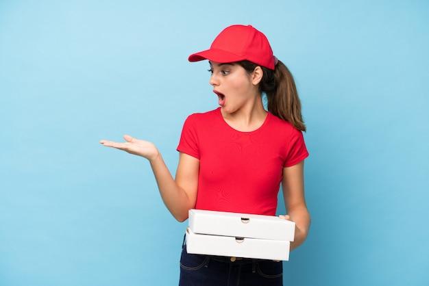 手のひらに想像上のcopyspaceを保持しているピザの壁を保持している若い女性