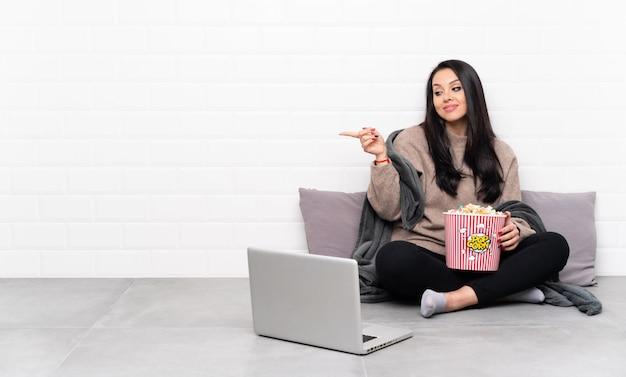 ポップコーンのボウルを保持していると挿入する手のひらに想像上のcopyspaceを保持しているラップトップで映画を見せて若いコロンビアの女性