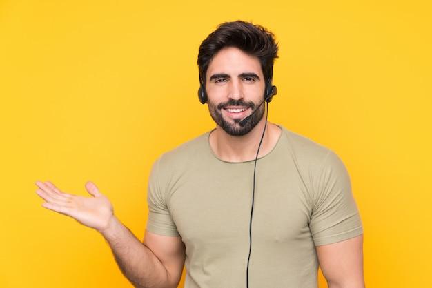 手のひらに想像上のcopyspaceを保持している孤立した黄色の壁を越えてヘッドセットを扱うテレマーケティング男