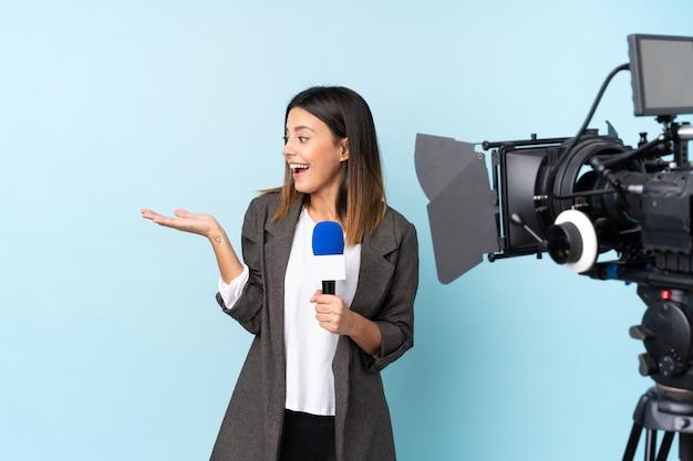 Репортер женщина, держащая микрофон и сообщения о новостях над синей стеной, держа copyspace мнимой на ладони