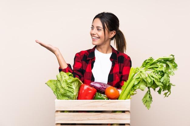 Фермер женщина, держащая свежие овощи в деревянной корзине, держащей воображаемый copyspace на ладони