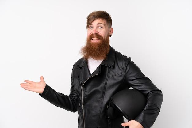 手のひらに想像上のcopyspaceを保持している孤立した白い壁にオートバイのヘルメットを保持している長いひげを持つ赤毛の男