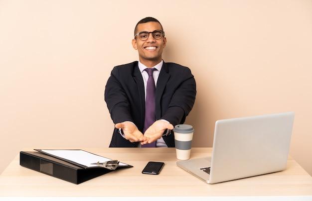 ノートパソコンと広告を挿入する手のひらに想像上のcopyspaceを保持している他のドキュメントと彼のオフィスで若いビジネスマン