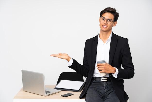 Бизнесмен в своем кабинете над белой стеной, держа на ладони copyspace мнимой