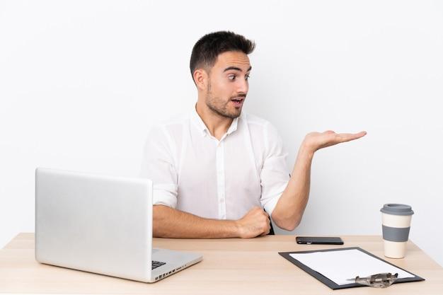 手のひらに想像上のcopyspaceを保持している職場で携帯電話を持つ若いビジネス男