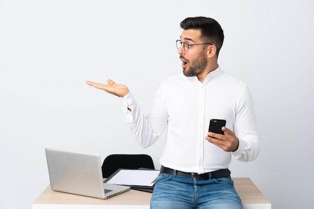 手のひらに想像上のcopyspaceを保持している携帯電話を保持している青年実業家