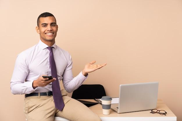 手のひらに想像上のcopyspaceを保持しているオフィスの若いビジネスマン