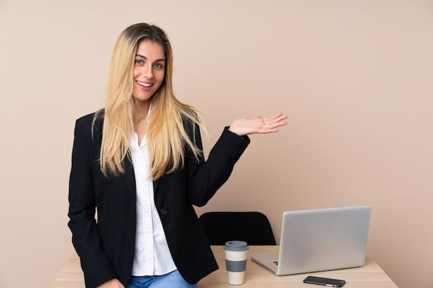 手のひらに想像上のcopyspaceを保持しているオフィスの若いビジネス女性