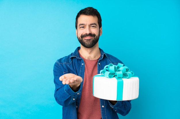 Молодой красавец с большой торт над изолированной синей стеной, держа воображаемое copyspace на ладони, чтобы вставить объявление