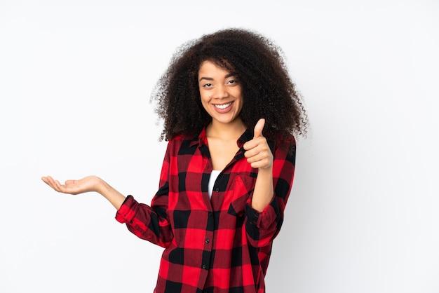 Молодая афро-американская женщина над изолированной стеной держа copyspace мнимое на ладони для того чтобы вставить объявление и с большими пальцами руки вверх