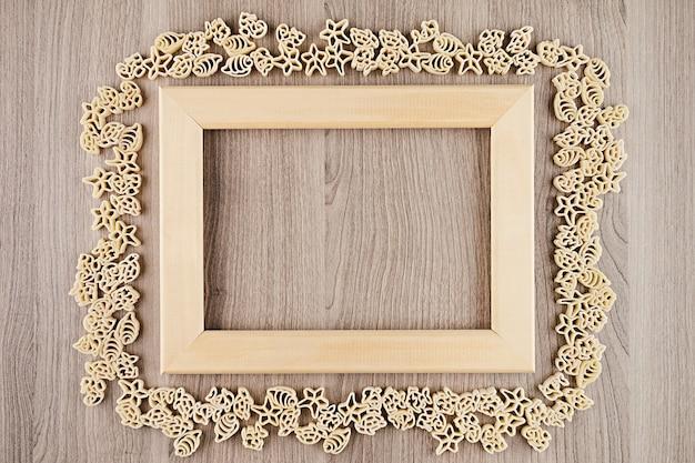 装飾的なフレームの背景として空copyspaceとベージュ茶色の木の板にイタリアの乾燥海パスタ