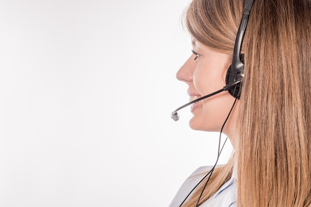 ヘッドセット、白い背景の上にスローガンまたはテキストメッセージのための空白のcopyspace領域で顧客サポート電話オペレータ。コンサルティングおよび援助サービスコールセンター