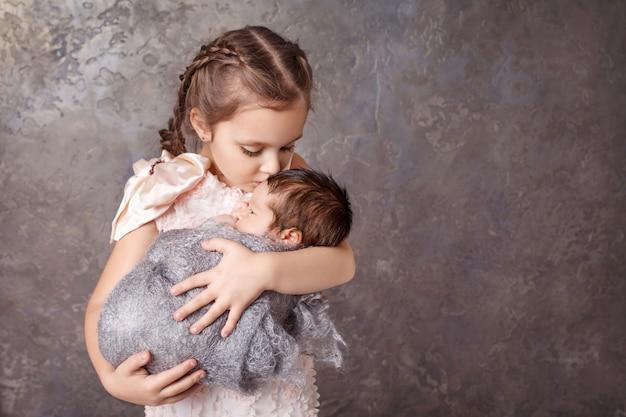 Милая девушка держит ее маленький брат. счастливая сестра целует новорожденного брата. copyspace