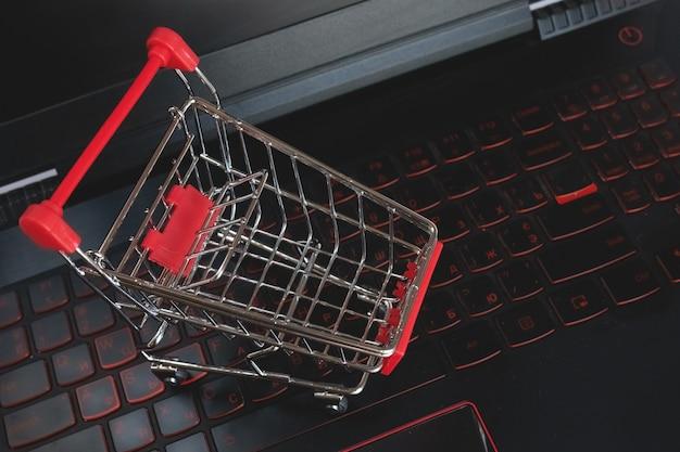 Покупки онлайн, корзина на черной клавиатуре. красная металлическая тележка на клавиатуре ноутбука. сервис покупок в интернете. предлагает доставку на дом. copyspace для текста.