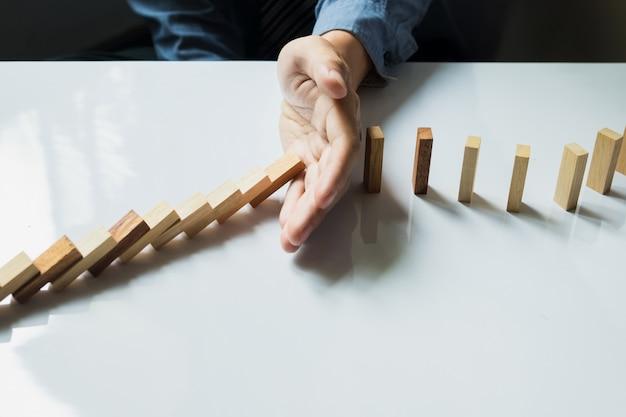 Бизнесмен ручная остановка домино непрерывная опрокидывание или риск с copyspace