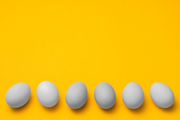 Белые яичка в ряд на дне желтой предпосылки с copyspace. пасха минималистичный дизайн концепции