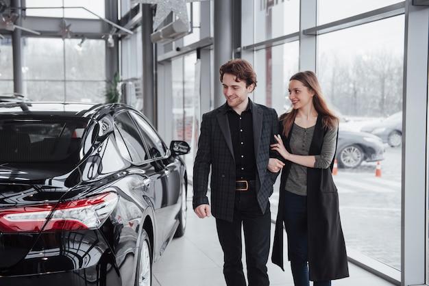 誇りに思う所有者。彼らの新しく購入した車の近くに立って抱いて美しい若い幸せなカップルが車のキーを見せて喜んで笑顔copyspace家族愛関係ライフスタイル購入消費主義