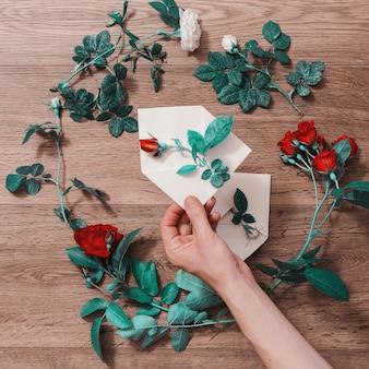 白い封筒を持っている手。封筒と白と赤のバラ。グリーティングカード。概念的な写真。結婚式の招待カード。バレンタインデー。フラット横たわっていた、トップビュー、copyspace
