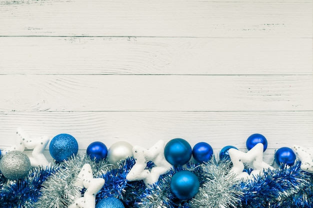 Новогодний фон с декоративной композицией из синих и серебряных елочные шары, белые звезды и мишура. с новым годом. copyspace