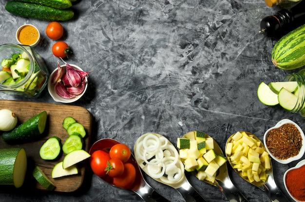 Овощи свежие овощи (огурцы, помидоры, лук, чеснок, укроп, зеленая фасоль) на сером фоне. вид сверху. copyspace