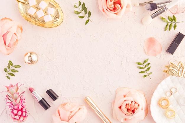 Взгляд сверху рабочего стола красоты блога женщины с copyspace, декоративной косметикой, цветками и листьями ладони, конвертом на розовой пастельной таблице