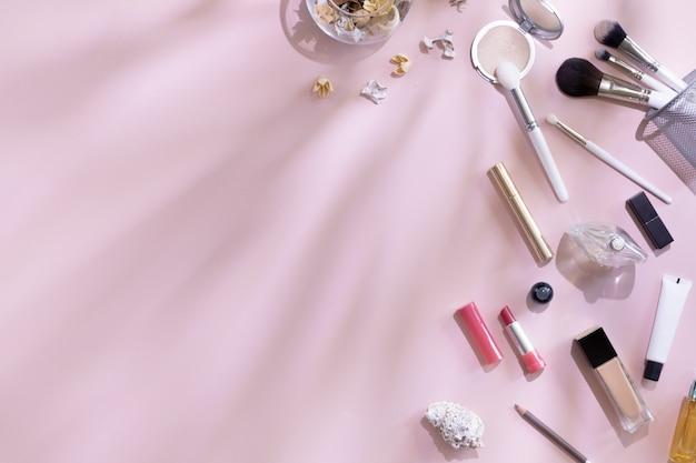 フラットレイアウトとメイクアップ製品と化粧品のトップビューの葉の影とハードライト、copyspaceとピンクの背景に設定。ブロガー、パステル女性ビジネスオフィステーブルデスクの美しさの概念