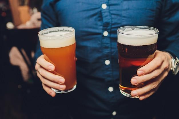 バーのレクリエーション醸造おいしいおいしいクールなさわやかな人々のお祝いのバーテンダーの作業で男の手にビールのガラスcopyspace完全なガラスのビールを握って男のショットをトリミング