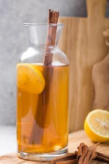 昆布茶またはサイダー発酵飲料。有益な細菌、シナモン、レモンcopyspaceとコンクリートの背景の側面図と冷たいお茶飲料。健康的な栄養のために。