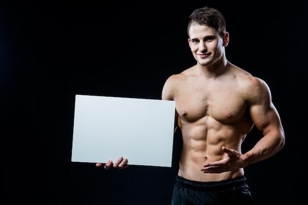 黒い壁に分離された空白の白いポスターと全身ボディービルダー。ハンサムな筋肉男の手で灰色のボードcopyspaceを保持しています。
