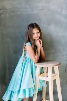 幸せ美しい美しいこぼれるような笑顔でかわいい素敵な魅力的な小さな女の子、彼女は青いドレスを着て、明るい灰色の背景、copyspaceに分離されたスツールに手を置いた