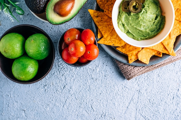 Чаша с мексиканским гуакамоле на старинном деревянном столе, в окружении помидоров, перца халапеоса, лайма и авокадо. copyspace
