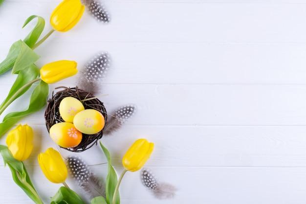Концепция пасхи - декоративное гнездо ивы с декоративными яичками, перо на белой предпосылке. copyspace для текста. плоская планировка