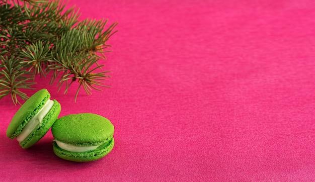 クリスマスツリーの枝の横にある赤い紙の背景にフォンダンと緑のマカロン。クローズアップ、copyspace。