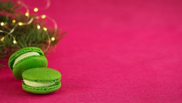 赤い紙の背景にフォンダンと緑のマカロン。ガーランドとクリスマスツリーの枝の近く。クローズアップ、copyspace。