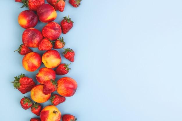 桃と青色の背景にイチゴ。 copyspace。