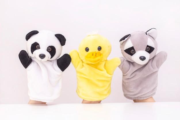 Кукольный театр на белом фоне. дружелюбные животные держатся за руки. концепция игры с детьми, дружба, семья, развлечения. няня развлекает детей. copyspace