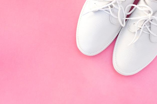 ピンクの背景に白のスニーカー。上からの眺め。 copyspace。テキストのための場所