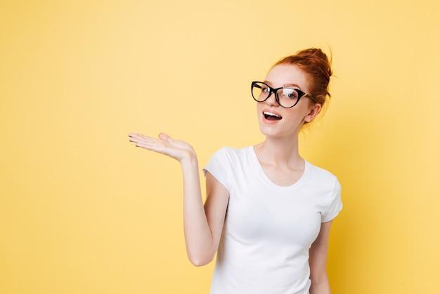 Счастливая рыжая женщина в очках держит невидимое copyspace на фунте
