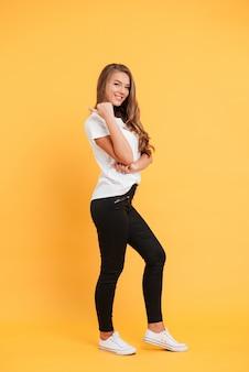Copyspaceを指している笑顔の美しい若い女性。
