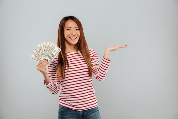 Усмехаясь азиатская женщина в свитере показывая деньги и держа copyspace на фунте над серой предпосылкой