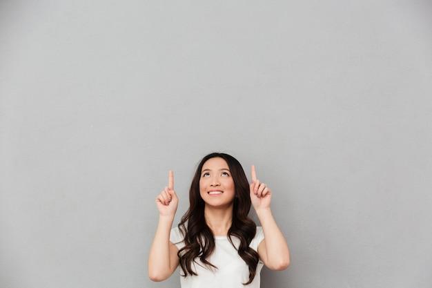 Изображение очаровательной приветливой женщины в повседневной футболке, указывающей пальцами вверх на тексте или продукте copyspace, изолированном над серой стеной